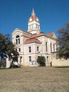 Bandera County Courthouse from a street level view on a clear afternoon, flanked by two oak trees on either side.