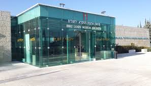 The front glass entrance to the Bible Land Museum, located in Jerusalem, on a bright, sunny day