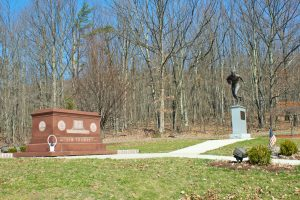 The brown granite tomb of Jim Thorpe, flanked to the right by a statue of him, on a bright and sunny fall day.