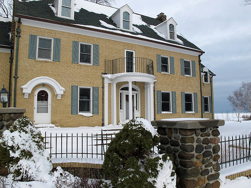 Yellow facade of the brick house with winter snow.